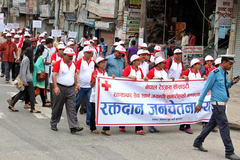 People with banners and placards participate in an awareness march organised on the occasion of 50th anniversary of the Nepal Red Cross Society's blood bank service,  at Putalisadak Chok, on Wednesday, July 27, 2016. Photo: RSS