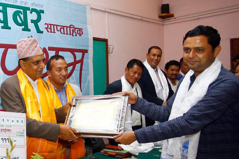 Minister for Culture, Tourism and Civil Aviation Ananda Prasad Pokharel honours THT journalist Rajan Pokhrel with the Wonchu Sherpa Memorial Award for raising issues related to mountaineering and the Sherpa community, in Kathmandu, on Thursday, July 14, 2016. Photo: THT Online