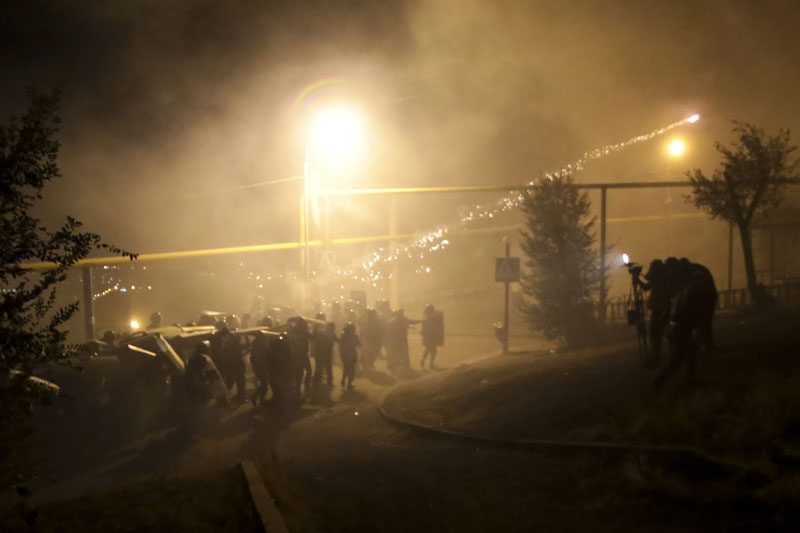 Riot police use light grenades as they confront anti-government protesters, supporters of the armed group who have been holed inside a police station, clash with police in Yerevan, Armenia, Friday, July 29, 2016. Photo: Aram Kirakosyan/PAN Photo via AP