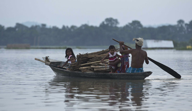 A flood affected family moves on a boat at Sildubi village, in the northeastern Indian state of Assam, Friday, July 29, 2016. Photo: AP