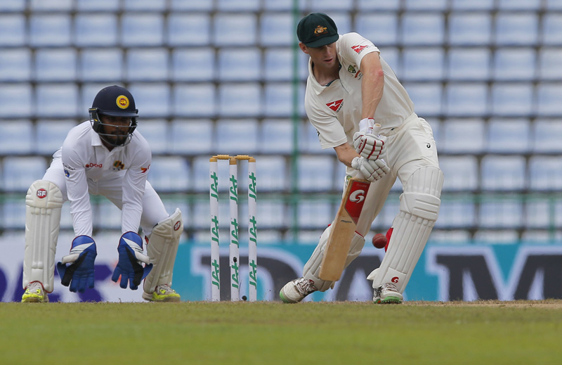 Australian cricketer Adam Voges plays a shot in front of Sri Lanka's Dinesh Chandimal during day two of the first test cricket match between Sri Lanka and Australia in Pallekele, Sri Lanka, Wednesday, July 27, 2016. Photo: AP