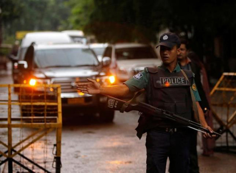 A policeman keep watch as a Japanese convoy drives, as relatives of victims of an attack on the Holey Artisan Bakery and the O'Kitchen Restaurant, visited the site, in Dhaka Bangladesh, July 4, 2016. Photo: Reuters