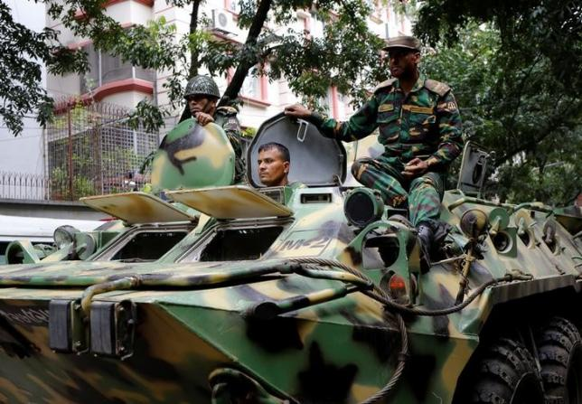 Army soldiers atop an armored military vehicle drive near the Holey Artisan restaurant after Islamist militants attacked the upscale cafe in Dhaka, Bangladesh, July 2, 2016.    REUTERS/Mohammd Ponir Hossain