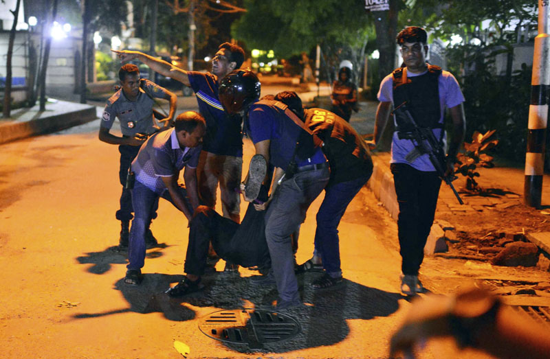 People help an unidentified injured person after a group of gunmen attacked a restaurant popular with foreigners in a diplomatic zone of the Bangladeshi capital Dhaka, Bangladesh, on Friday, July 1, 2016. A group of gunmen attacked a restaurant popular with foreigners in a diplomatic zone of the Bangladeshi capital on Friday night, taking hostages and exchanging gunfire with security forces, according to a restaurant staff member and local media reports. Photo: AP