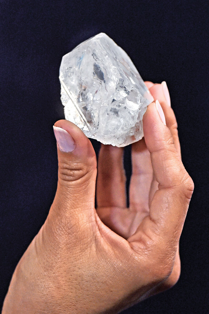 A model posing with an uncut 1109-carat diamond named 'Lesedi La Rona', at Sotheby's auction house in London, on June 14, 2016. The world's largest uncut diamond failed to sell at auction in London on Wednesday as bids failed to reach its reserve price of over $70 million. Photo: AFP