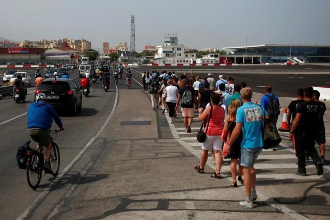 Pedestrians, drivers and bikers cross the tarmac at Gibraltar International Airport as they leave Gibraltar at its border with Spain (rear), in the British overseas territory of Gibraltar, historically claimed by Spain, June 27, 2016, after Britain voted to leave the European Union in the EU Brexit referendum. REUTERS/Jon Nazca/Files