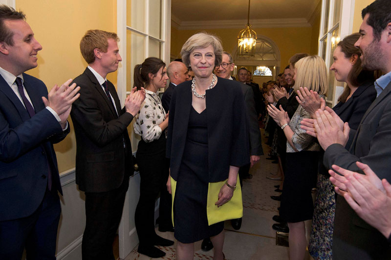 Staff applaud as Britain's new Prime Minister Theresa May, and her husband Philip, walk into 10 Downing Street after May had met Queen Elizabeth in Buckingham Palace, in central London, Britain on July 13, 2016. Photo: Reuters