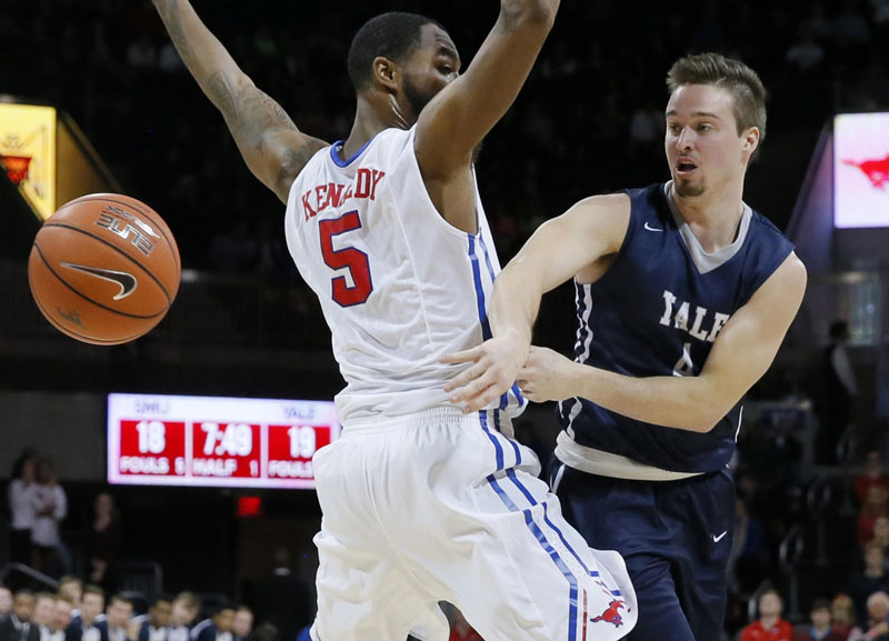 FILE - Yale's Jack Montague (right) passes the ball around SMU's Markus Kennedy during an NCAA college basketball game in Dallas, on November 22, 2015. Photo: AP
