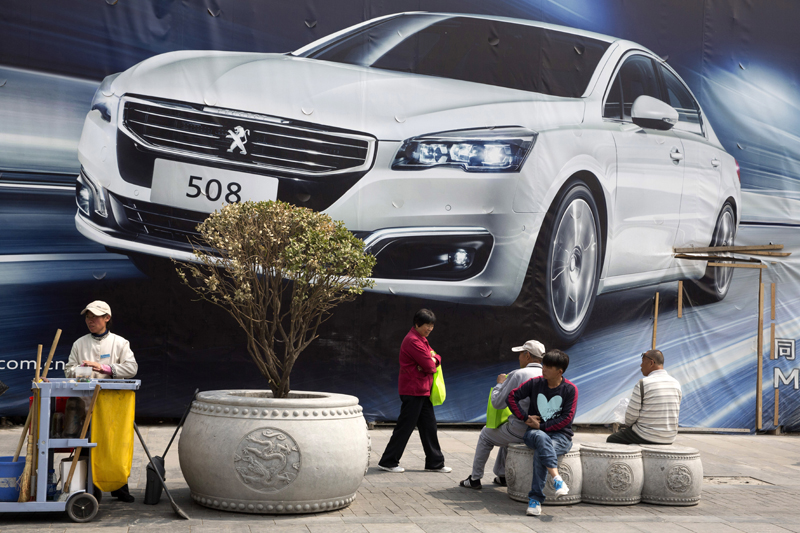 FILE - In this April 13, 2016, file photo, visitors to a retail area walk past an ad for a car in Beijing. Photo: AP