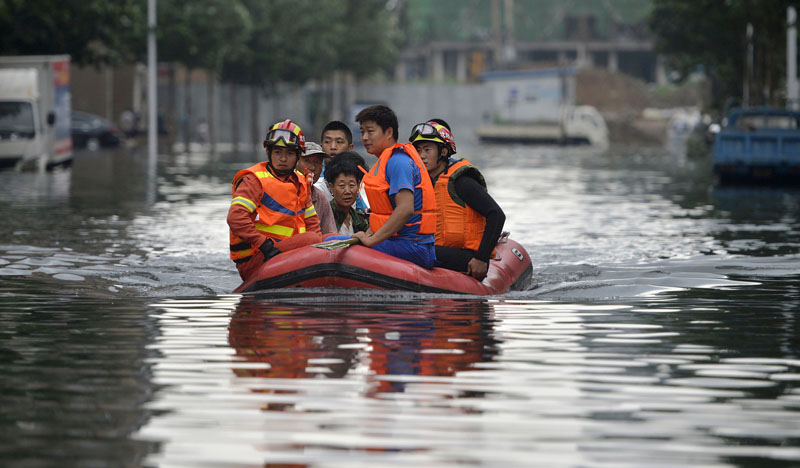 Rescuers use a raft to transport people along a flooded street in Shenyang in northeastern China's Liaoning Province, on  Thursday, July 21, 2016. Photo: Chinatopix Via AP)