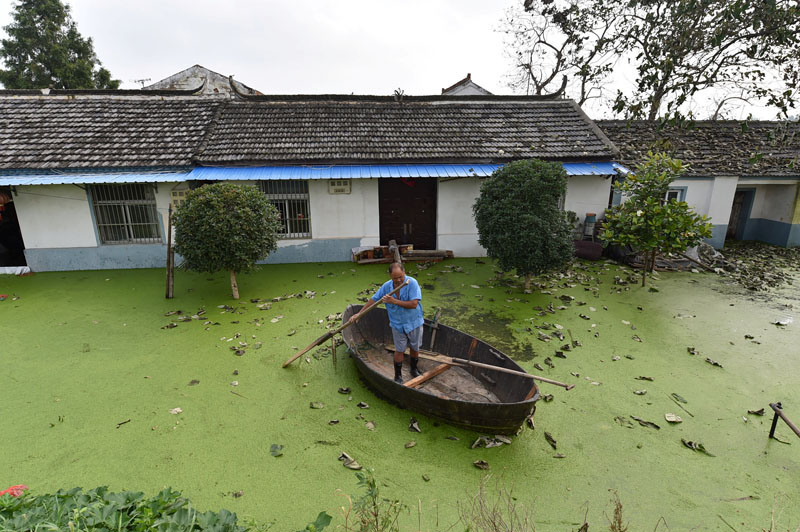 A man rows a boat near a flooded house in Hefei, Anhui Province, China, on July 9, 2016. Photo: Reuters