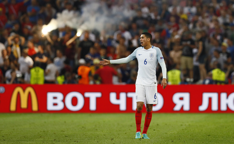 England's Chris Smalling looks on as a flare is let off at Stade Vu00e9lodrome in Marseille on June 11, 2016. Photo: Reuters