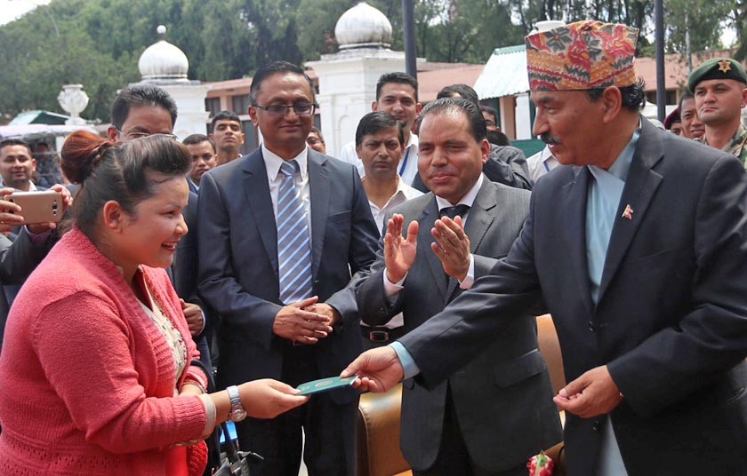 Deputy Prime Minister and Minister for Foreign Affairs Kamal Thapa hands over a passport to Chandrakali Budathoki of Dang that was made in 10 minutes at the Department of Passport in Kathmandu, on Sunday, July 3, 2016. Photo: RSS