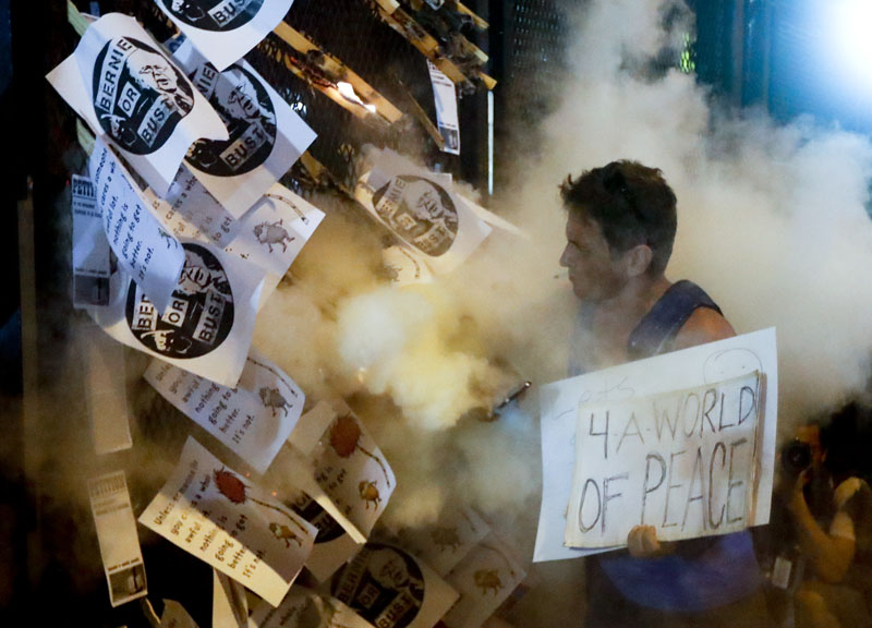 A demonstrator starts a fire during a protest in Philadelphia, on Tuesday, July 26, 2016, during the second day of the Democratic National Convention. Photo: AP