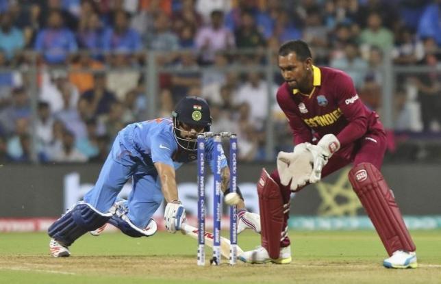 Cricket - West Indies v India - World Twenty20 cricket tournament semi-final - Mumbai, India - 31/03/2016. India's Virat Kohli (L) dives successfully to make his crease past West Indies wicketkeeper Denesh Ramdin.  REUTERS/Shailesh Andrade - RTSD076