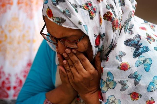 A woman mourns for the victims who were killed in the attack on the Holey Artisan Bakery and the O'Kitchen Restaurant, at a makeshift memorial near the attack site, in Dhaka, Bangladesh, July 5, 2016. REUTERS/Adnan Abidi
