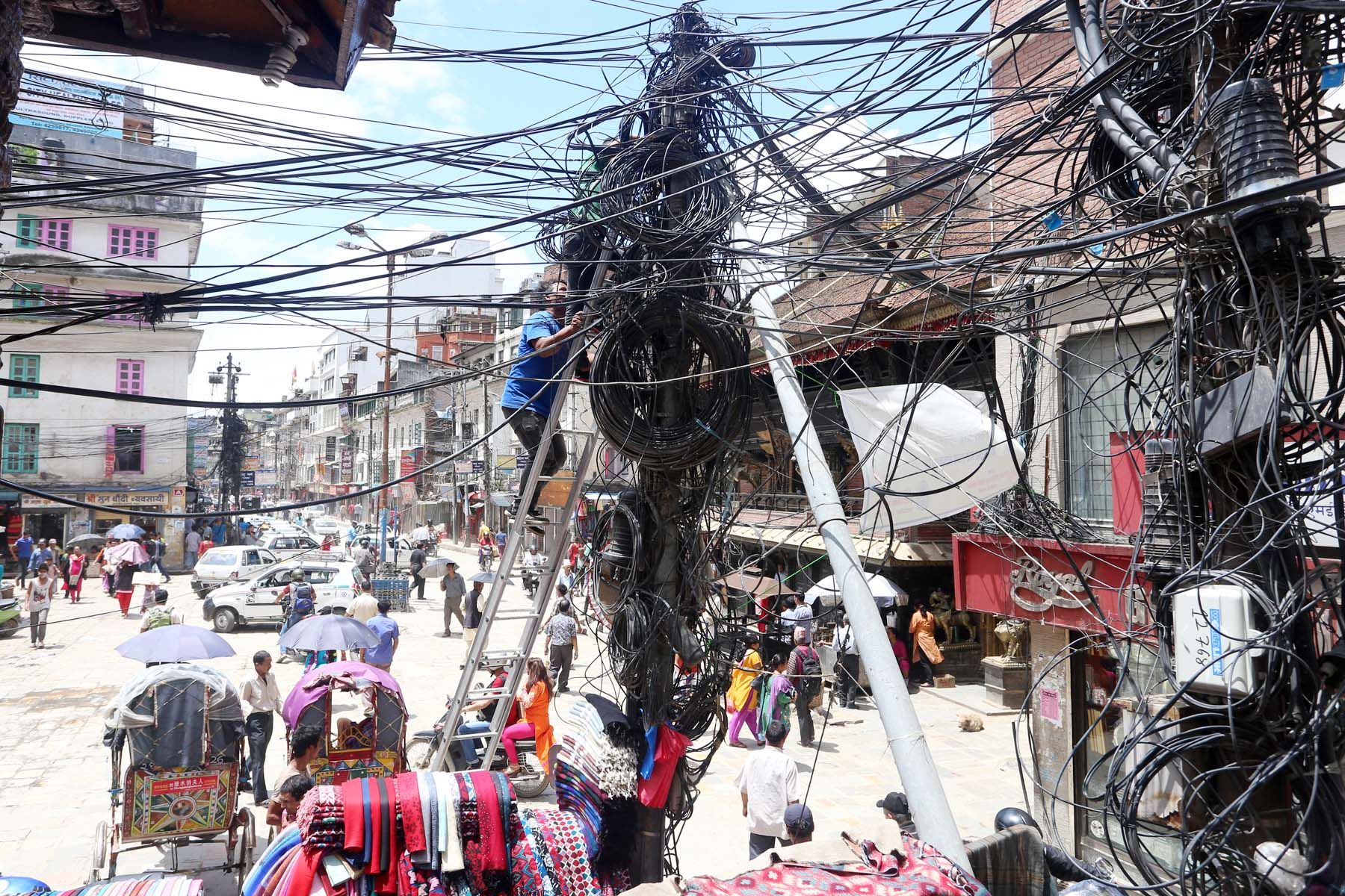 A man climbs a ladder to repair electrical wires on a utility pole in Indrachok of Kathmandu on Friday, June 15, 2016. Photo: RSS