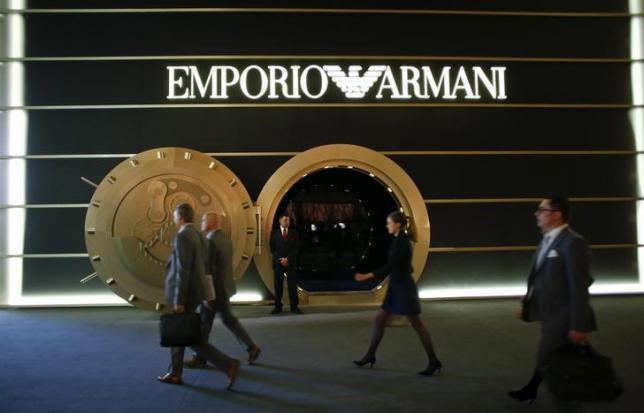 People walk past the exhibition stand of Italian watchmaker Emporio Armani at Baselworld fair in Basel March 18, 2015. REUTERS/Arnd Wiegmann/Files