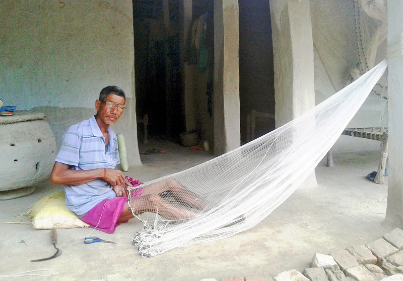 A man weaves a fishing net in Kanchanpur district, on Monday, July 4, 2016. Photo: RSS