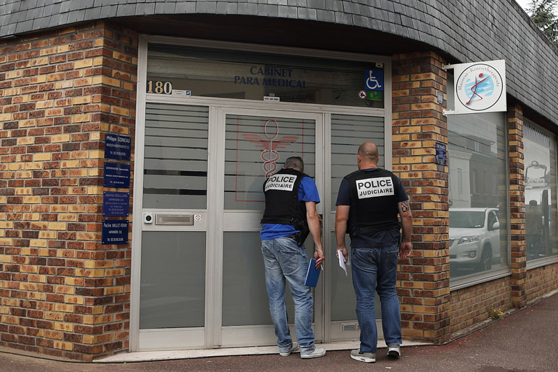 French police officers goes door to door to investigate at Saint-Etienne-du-Rouvray, Normandy, France, a day after an hostage taking left a priest dead on Wednesday, July 27, 2016. Photo: AP