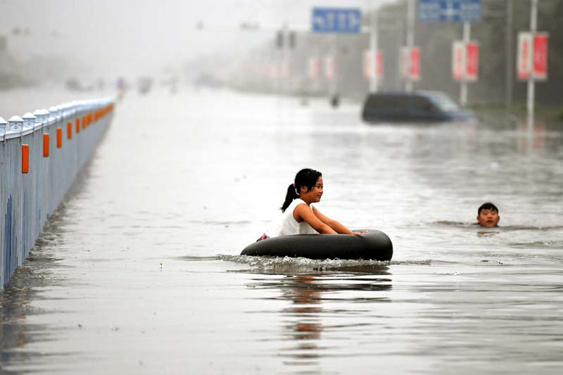 A girl sitting on a tyre plays at a flooded street, as a man swims near her in Xinxiang, Henan Province, China, on July 9, 2016. Photo: Reuters