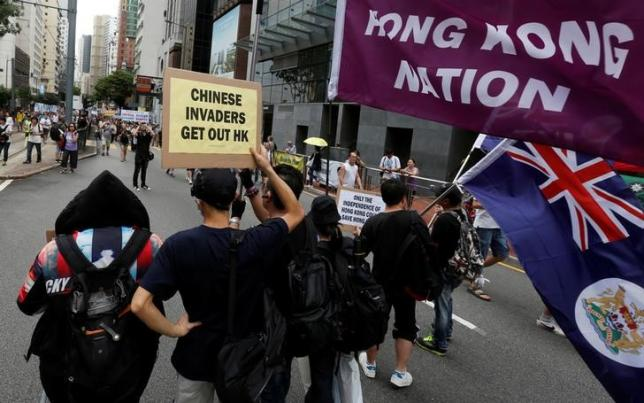 Pro-independence protesters carry placard and flags during a pro-democracy march on the day marking the 19th anniversary of Hong Kong's handover to Chinese sovereignty from British rule, in Hong Kong July 1, 2016.  REUTERS/Bobby Yip