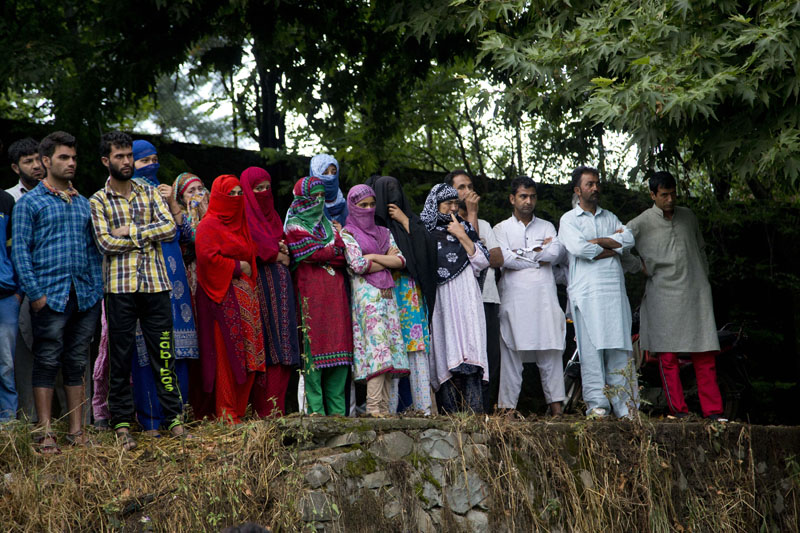 Kashmiri villagers watch the funeral procession of Burhan Wani, chief of operations of Indian Kashmir's largest rebel group Hizbul Mujahideen, in Tral, some 38 Kilometres (24 miles) south of Srinagar, Indian controlled Kashmir, on Saturday, July 9, 2016. Photo: AP