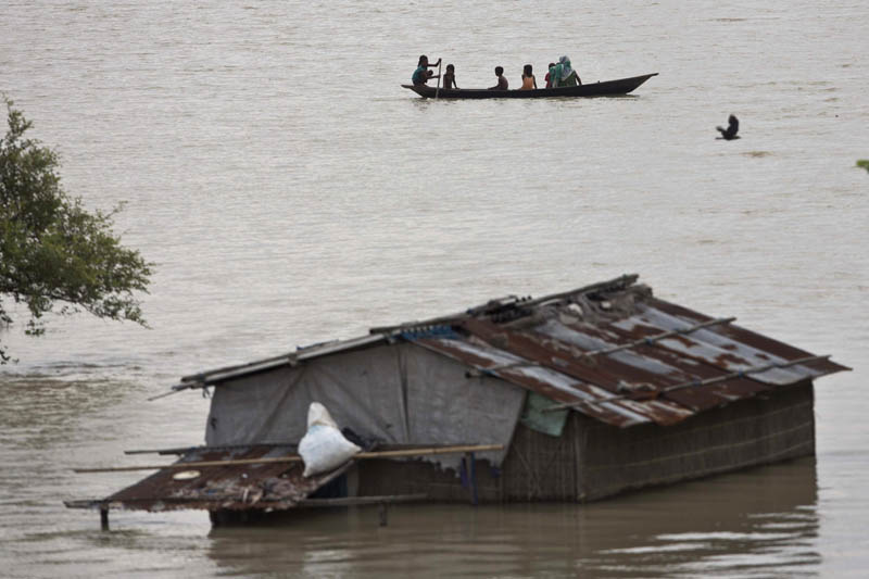An Indian family moves on a boat after heavy monsoon rains flooded Burhaburhi village, east of Gauhati, Assam, India on Sunday, July 24, 2016. Photo: AP
