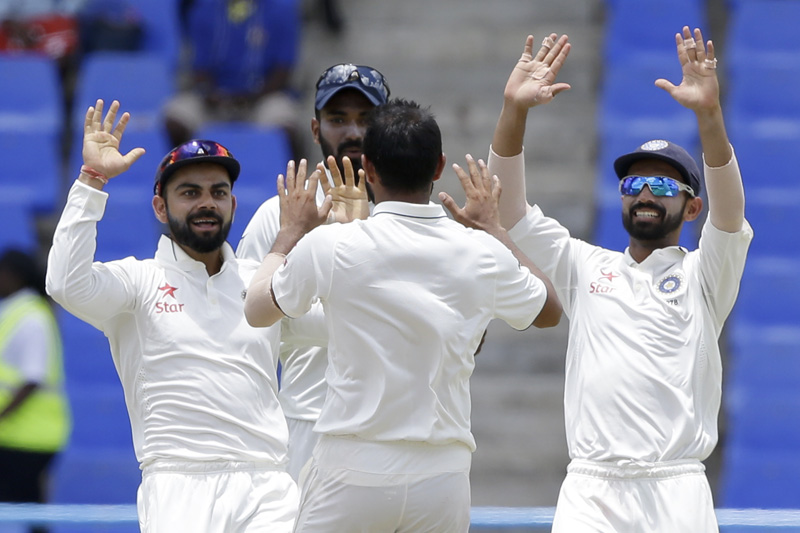 India's bowler Mohammed Shami, back to camera, celebrates with team captain Virat Kohli, left, and teammates taking the wicket of West Indies' Darren Bravo during day three of their first cricket Test match at the Sir Vivian Richards Stadium in North Sound, Antigua, Saturday, July 23, 2016. Photo: AP