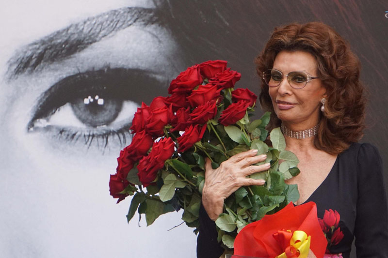 Sophia Loren holds a bunch of red roses as she stands in front a giant portrait of herself after being awarded with the honorary citizenship of Naples, Italy, Saturday, July 9, 2016. Photo: Cesare Abbate/ANSA Via AP