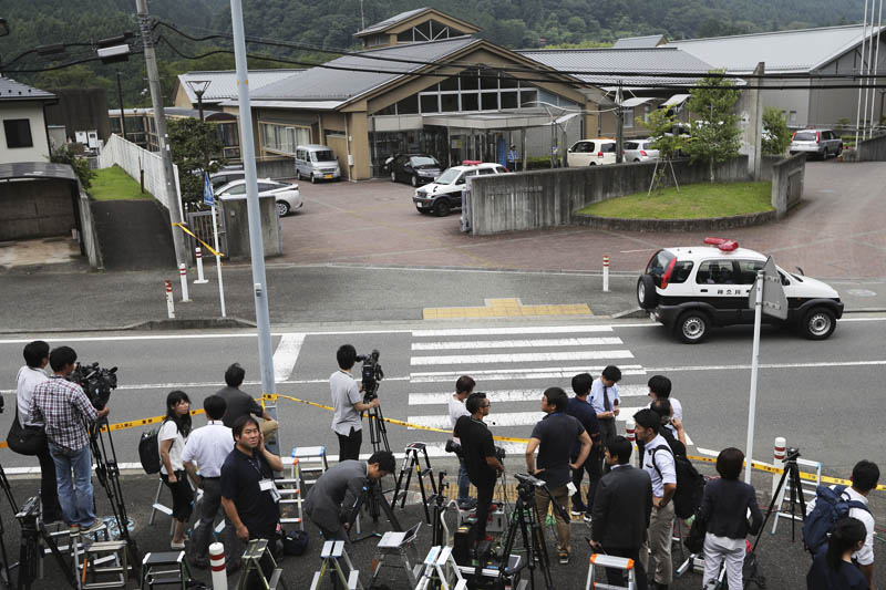 Journalists gather in front of Tsukui Yamayuri-en, a facility for the handicapped where a number of people were killed and dozens injured in a knife attack in Sagamihara, outside Tokyo on Tuesday, July 26, 2016. Photo: AP