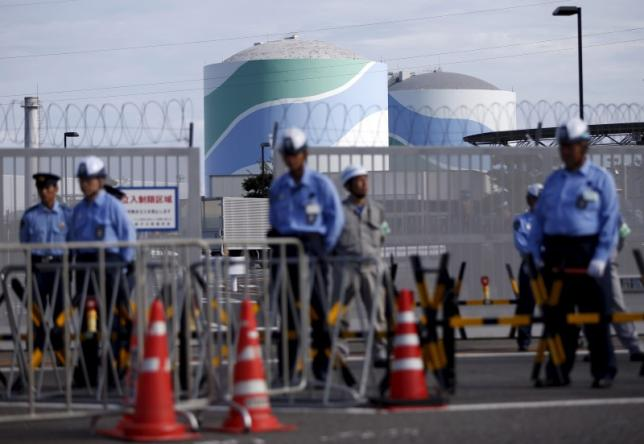 Security personnel stands guard in front of an entrance gate of Kyushu Electric Power's Sendai nuclear power station in Satsumasendai, Kagoshima prefecture, Japan, August 7, 2015. Japanese utility Kyushu Electric Power said on August 17 that it was monitoring activity at a volcano near its Sendai nuclear plant, but did not need to take any special precautions after authorities warned of the risk of a larger-than-usual eruption. The No.1 (L) and No.2 reactor buildings are seen behind them. Picture taken August 7, 2015. REUTERS/Issei Kato - RTX1OG1U