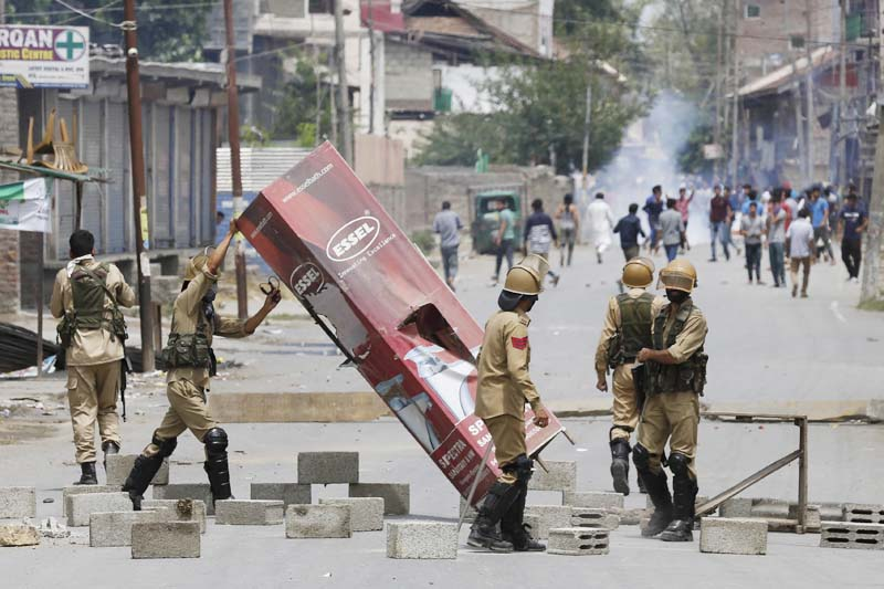 Indian policemen remove roadblock set up by protesters who were reacting to the killing of rebel leader Burhan Wani in Srinagar, Indian controlled Kashmir on July 9, 2016. Photo: AP