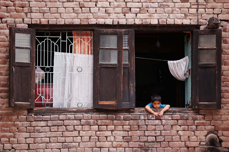 A boy looks out from a window of his house during a curfew in Srinagar on July 17, 2016. Photo: Reuters