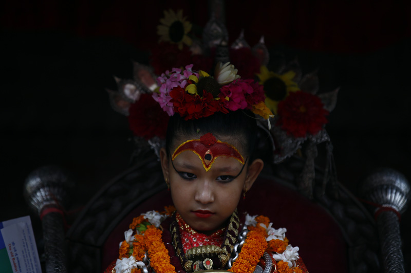Living Goddess Kumari looks on as devotees (unseen) offer prayers to her during the chariot procession of Rato Machindranath festival in Kumaripati, Lalitpur on Tuesday, July 26, 2016. Rato Machhindranath is worshipped as the god of rain and good harvest by both Hindus and Buddhists.