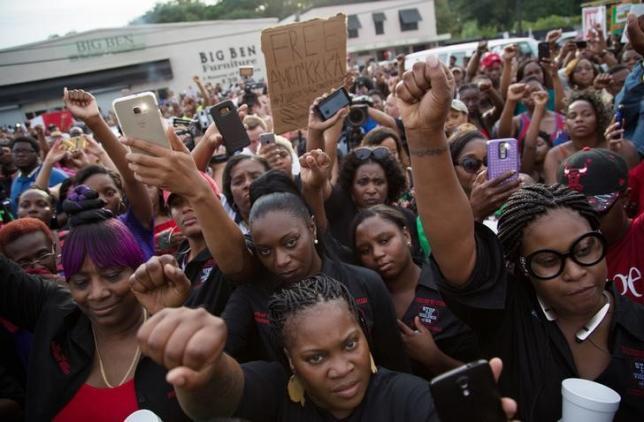 Community members attend a vigil in memory of Alton Sterling, who was shot dead by police, at the Triple S Food Mart in Baton Rouge, Louisiana, U.S. July 6, 2016. REUTERS/Jeffrey Dubinsky