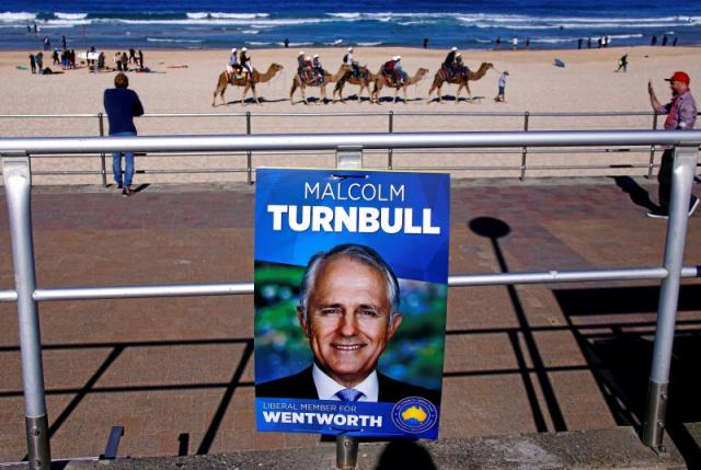 Tourists ride camels along Bondi Beach near a poster promoting the Australian Prime Minister Malcolm Turnbull in front of a voting station, located in the Bondi Surf Lifesavning Club, in Sydney, Australia. nnREUTERS/David Gray