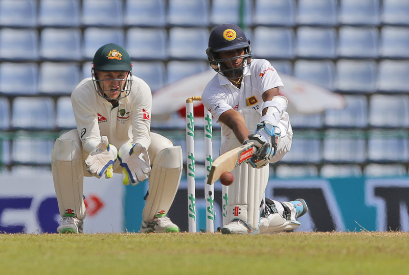 Sri Lanka's Kusal Mendis plays a shot as Australian wicketkeeper Peter Nevill watches bats on day three of the first test cricket match between Sri Lanka and Australia in Pallekele, Sri Lanka, Thursday, July 28, 2016. Photo: AP