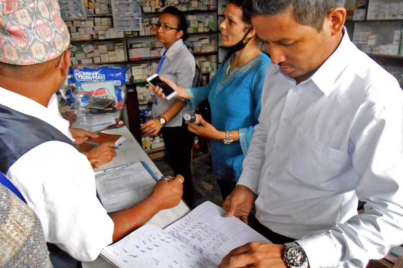 An official of the inspection team deployed from the Ministry of Supplies inspects a drugstore in Capital, on Sunday, July 10, 2016. Photo: RSS