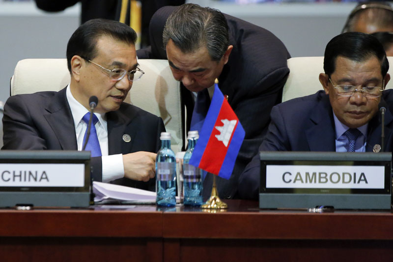 Chinese Premier Li Keqiang (left) talks with Foreign Minister Wang Yi, center, as he and Cambodia's Prime Minister Hun Sen (right) attend the opening session of the Asia-Europe Meeting (ASEM) summit in Ulaanbaatar, Mongolia on Friday, July 15, 2016.   Phto: Damir Sagolj/Pool Photo via AP