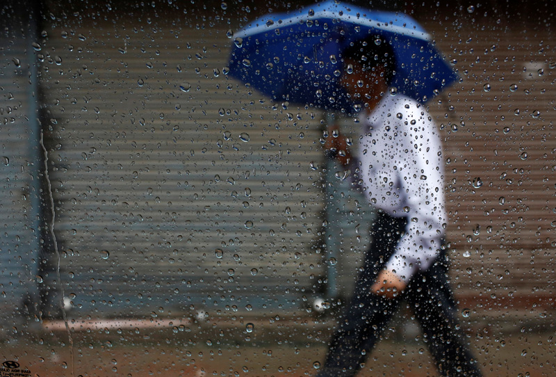 Raindrops are pictured on the window of a car as a man holding an umbrella passes by during the rainfall in Kathmandu, Nepal July 1, 2016. REUTERS