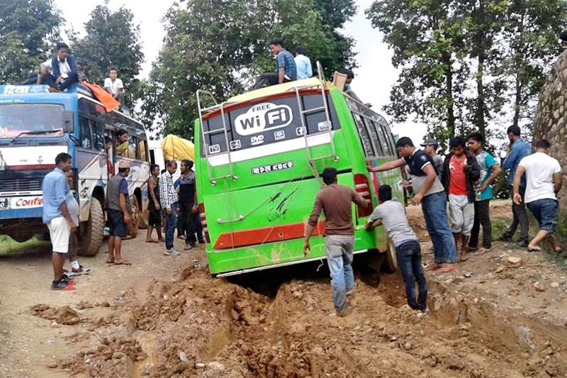 People pushing a bus struck in a muddy road at Golabhanjyang, Dhading ,on Friday, July 8, 2016. Photo: THT