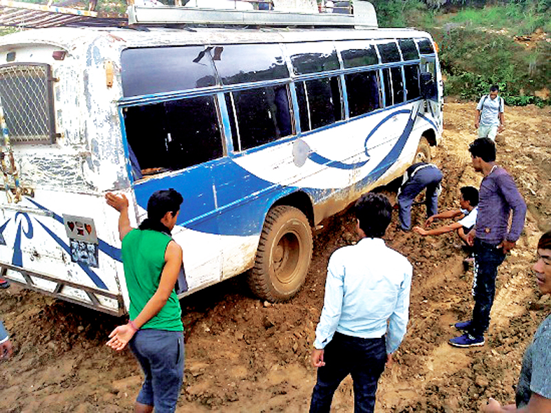 Passengers trying to take a bus out of the slush after it got stuck along the Hile-Bhojpur-Naradmani Thulung Auxiliary road section, in Bhojpur, on Thursday, July 21, 2016. Photo: THT