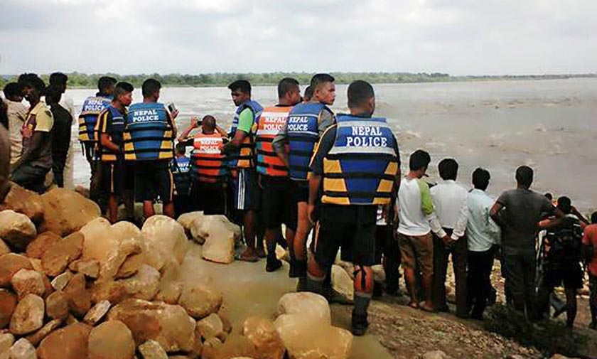 Security personnel and others look at the swollen Narayani River near the Gandak Barrage in Nawalparasi district on Tuesday, July 26. After water level in the mighty river crossed danger mark, all sluice gates in the barrage were opened. Photo: RSS