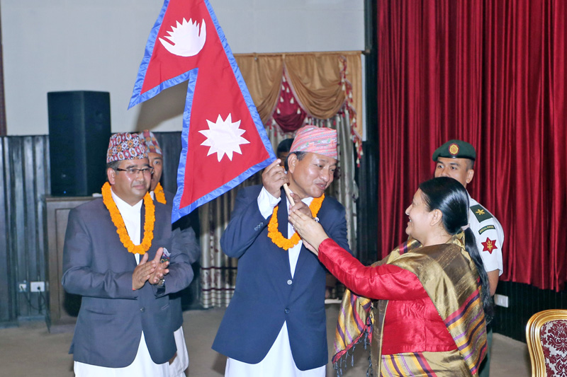 President Bidya Devi Bhandari (right) hands over the national flag to Nepali team leader Keshav Kumar Bista (centre), member-secretary of the National Sports Council, representing Nepal at the Rio Games in Brazil, prior to team's departure at Seetal Niwas in Kathmandu, on Tuesday, july 26, 2016. Photo: RSS