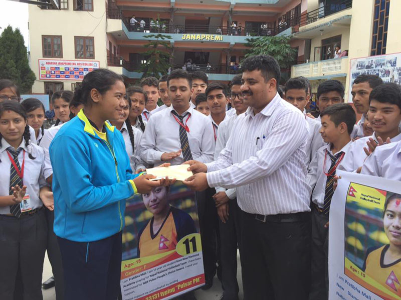 Principal of Janapremi Higher Secondary School Nilesh Acharya handing over Rs 5,000 to national volleyball team member Pratibha Mali to help her in Peopleu2019s Choice Award campaign in Bhaktapur, on Tuesday, July 19, 2016. Photo: THT