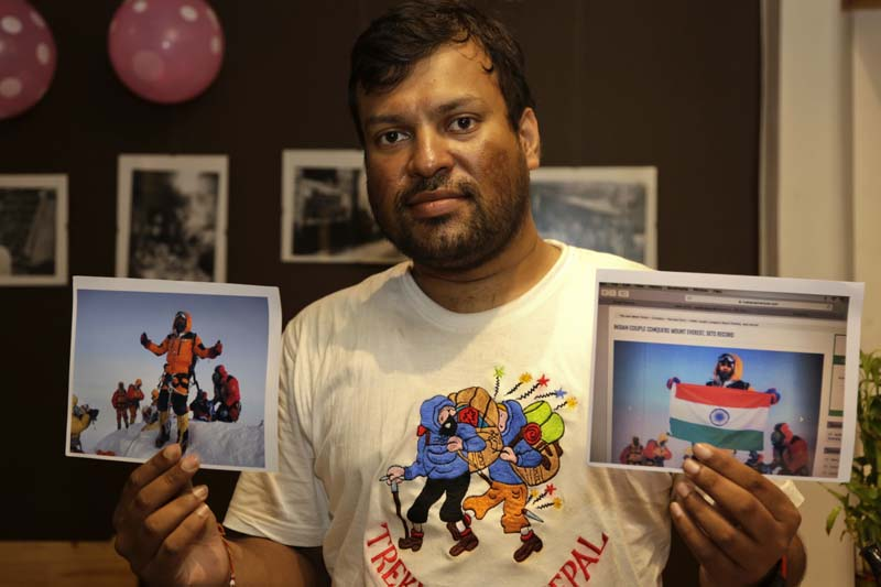 Indian climber, Satyarup Sidhantha holds on his right hand a photograph that shows him on Mount Everest, along with what he says is an altered version of the same used by an Indian couple to make it appear they were on the summit, as he displays them for the Associated Press in Kolkata, India, Monday, July 4, 2016. Photo: AP
