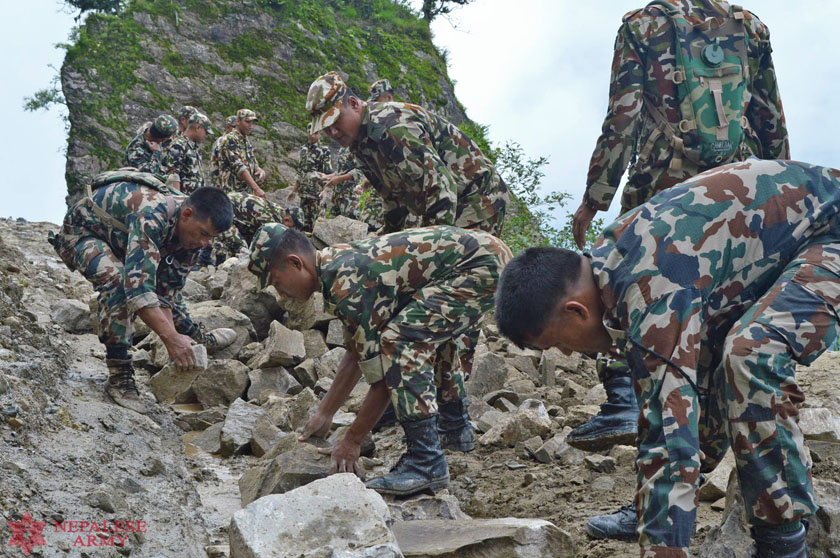 Army personnel from the Narayandal Battalion clear out the debris from the road at Mulkharka, Ramche-2 of Rasuwa on Thursday July 14, 2016. The incessant rainfall has triggered landslides in various parts of the country. Photo: Nepal Army