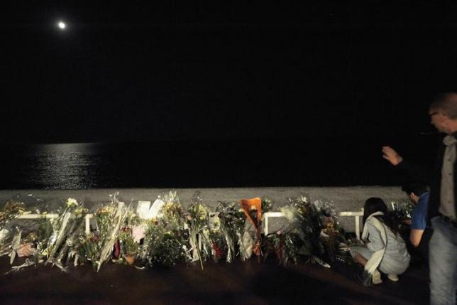 The moon is reflected on the Mediterranean Sea as flowers left in tribute at makeshift memorials to the victims of the truck attack are placed along the Promenade des Anglais in Nice, France, July 18, 2016. REUTERS/Jean-Pierre Amet