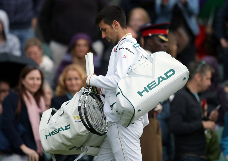 Novak Djokovic of Serbia leaves the court as rain stops his men's singles match against Sam Querrey of the US on day five of the Wimbledon Tennis Championships in London, on Friday, July 1, 2016. Photo: AP